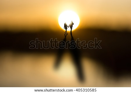 Young couple holding hands, back lit by sun at dawn, casting long shadows - stock photo