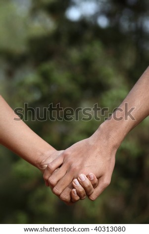 Young couple holding hands (closeup) while outdoors in a park - stock photo