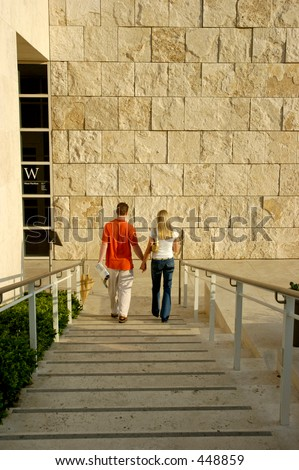Young couple holding hands going down a set of stairs - stock photo