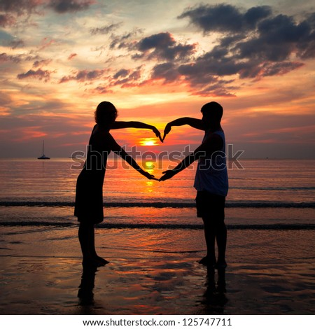 Young couple holding hands heart-shaped on the sea beach at sunset. - stock photo
