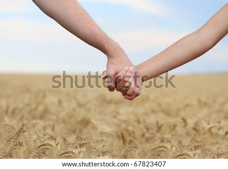 Young couple holding hands in the field. Close-up - stock photo