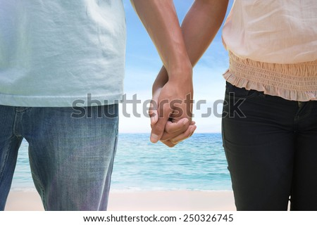 Young couple holding hands in the park against beach scene
