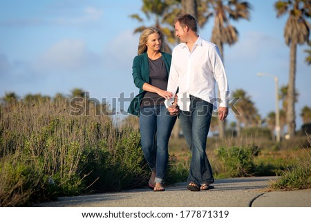 Young couple holding hands on a walk - stock photo