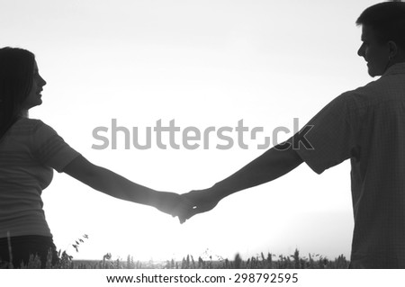 Young couple holding hands on sunny summer day. - stock photo