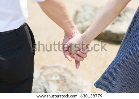 Young couple holding hands on the beach