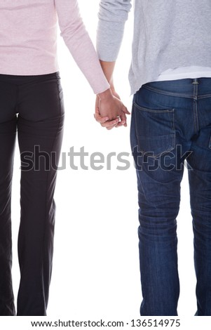 Young Couple Holding Hands Over White Background - stock photo