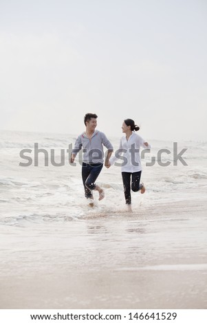 Young couple holding hands running by the waters edge on the beach, China