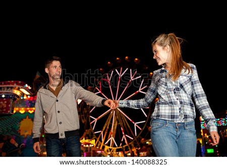 Young couple holding hands while visiting an amusement park arcade at night, with colorful lights and funfair rides around them. - stock photo