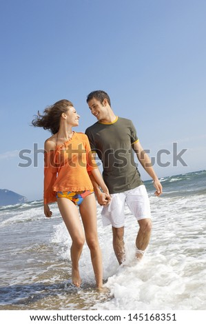 Young couple holding hands while walking in water at beach - stock photo