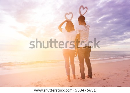 Young couple holding hands with heart-shaped foam over head his at beach sunset enjoying romance and sun in love on romantic summer holidays
