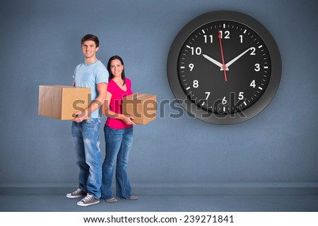 Young couple holding moving boxes against dark room - stock photo