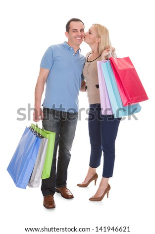 Young Couple Holding Shopping Bag Over White Background