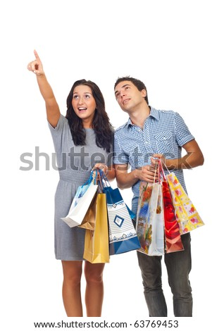 Young couple holding shopping bags ,woman pointing and both looking up isolated on white background - stock photo