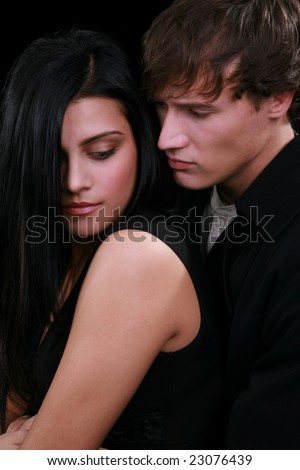 Young Couple Holding together Low Key Portrait on Dark Background - stock photo