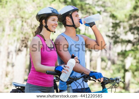Young couple holding water bottle while riding bicycle at forest - stock photo