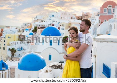 young couple honeymoon on the most romantic island Santorini, Greece. Sunset in the city Oia - stock photo