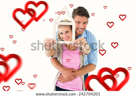 Young couple hugging and holding house outline against hearts - stock photo