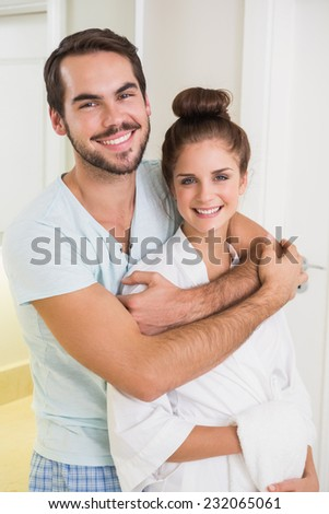 Young couple hugging and smiling at each other at home in the bathroom - stock photo