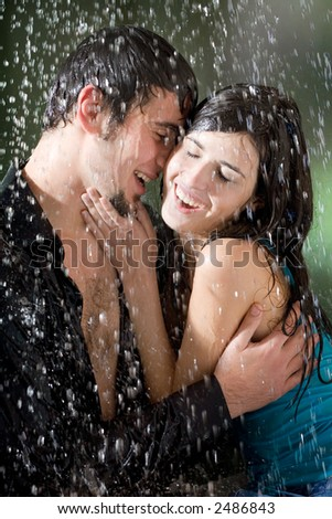 Young couple hugging and under a rain, in passion - stock photo