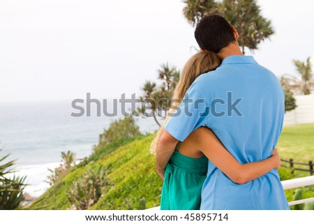 young couple hugging, background is sea view