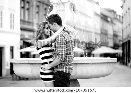 Young couple hugging by the fountain - stock photo