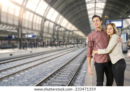 Young couple hugging each other on a train station, waiting for a train to arrive, ready to go places. - stock photo