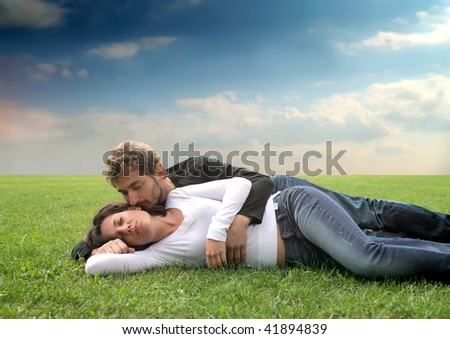 young couple hugging in a grass field - stock photo
