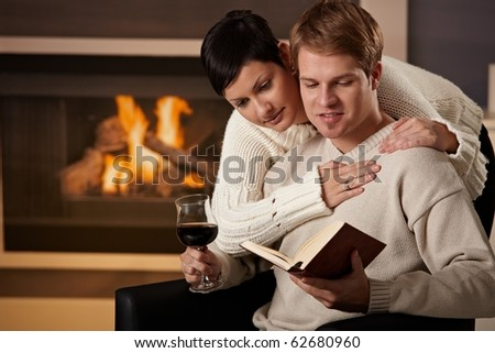 Young couple hugging in front of fireplace at home, reading book.