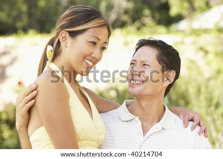 Young Couple Hugging In Garden - stock photo