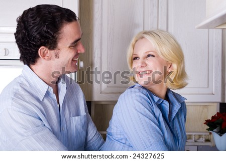young couple hugging in the kitchen - stock photo