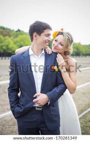 Young couple hugging in wedding gown. Bride holding bouquet of flowers