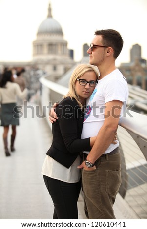 young couple hugging on Millennium Bridge