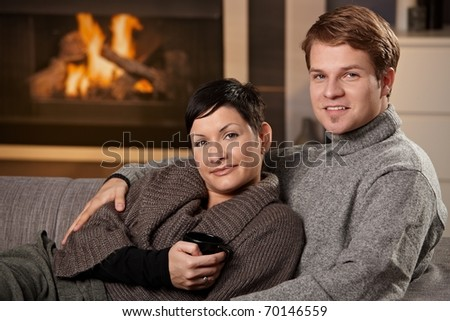 Young couple hugging on sofa in front of fireplace at home, looking at camera, smiling.?