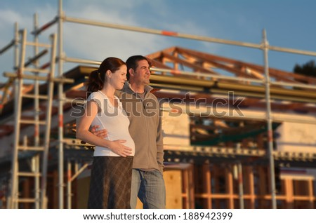 Young couple hugging outside their new home. Concept buying a new house. - stock photo