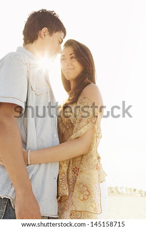 Young couple hugging together and standing on a white sand beach against a sunny sky with the sun rays filtering through them with golden light while having a romantic moment. - stock photo