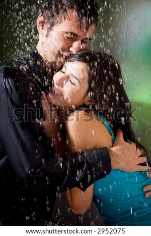 Young couple hugging under a rain, in passion