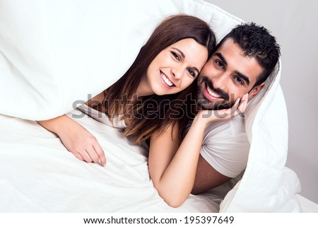 Young couple hugging while lying in bed in the morning - stock photo
