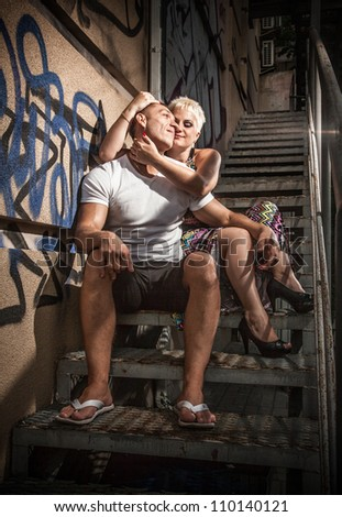 Young couple hugging while sitting on metal stairway