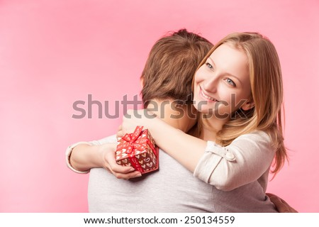 Young couple hugging with wrapped present. woman embracing man and holding present with ribbon. Isolated over pink background.  - stock photo