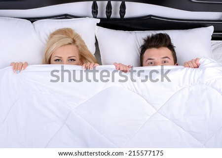 Young couple in a bed, looking out from under blanket - stock photo