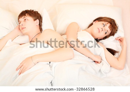 Young couple in a bedroom at home. Family conflict. - stock photo