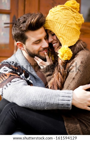Young couple in a cabin in romantic scape in winter - stock photo