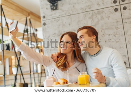 Young couple in a cafe taking selfie. Selective focus on man face. - stock photo