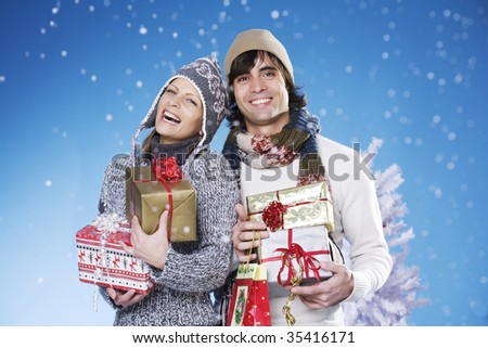 young couple in a joyful mood with lots of presents - stock photo
