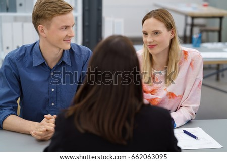 Young couple in a meeting with a broker or agent sitting at a table with her in the office in a view from behind her back