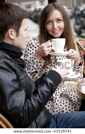 Young couple in a Parisian street cafe, drinking coffee - stock photo