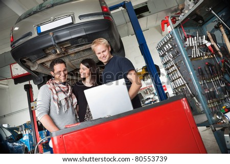 Young couple in auto repair shop standing with mechanic looking at laptop - stock photo