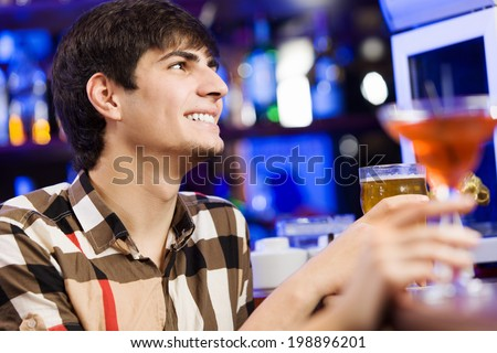 Young couple in bar having drinks and talking
