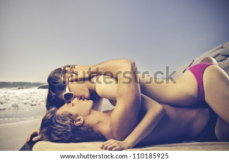 Young couple in bathing suit kissing at the seaside - stock photo