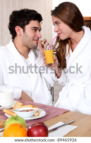 young couple in bathrobe drinking orange juice out of straw - stock photo